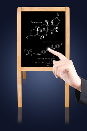 Hand pushing science formula on the black board. photo