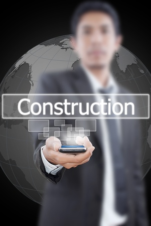 Businessman putting mobile with construction word. photo