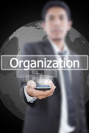 Businessman putting mobile with organization word. photo