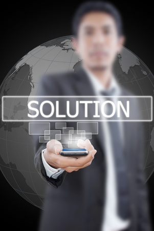 Businessman putting mobile with solution word. photo