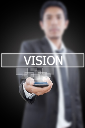 Businessman putting mobile with vision word. photo