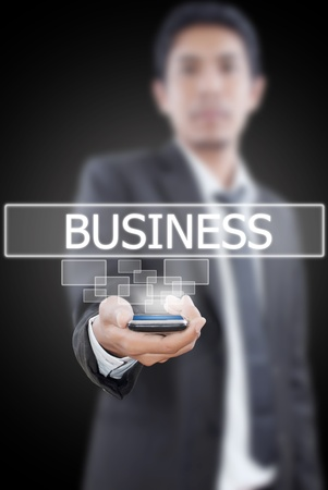 Businessman putting mobile with business word. photo