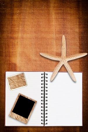 Star fish and notebook on the wood texture. photo