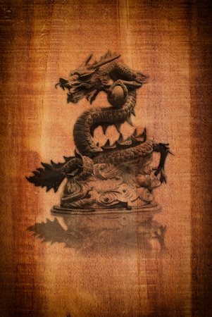 dragon head: Dragon statue on the wood texture. Stock Photo