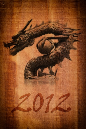 Dragon statue on the wood texture for new year 2012. photo