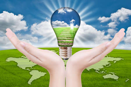 Hand putting light bulb for save world. Stock Photo - 11923840