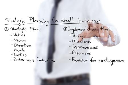 planeaci�n estrategica: Hombre de negocios empujando la planificaci�n estrat�gica de negocios en la pizarra.