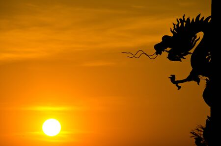 Dragon statue silhouette with sunset. photo