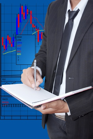 Businessman write on notebook for trade stock market graph  photo
