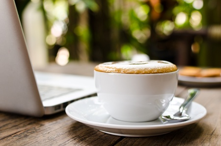Coffee cup and laptop on the wood texture, selective focus on coffee cream Stock Photo - 13511474