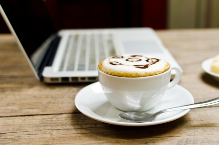 Coffee cup and laptop on the wood texture, selective focus on coffee cream  Stock Photo