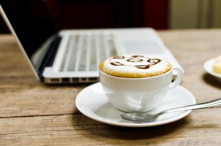 internet cafe: Taza de caf� y un ordenador port�til en la textura de madera, foco selectivo sobre crema de caf� Foto de archivo