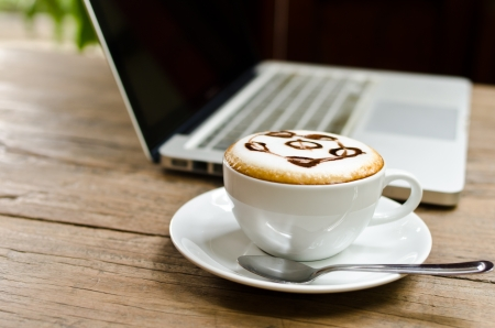 Coffee cup and laptop on the wood texture, selective focus on coffee cream  photo