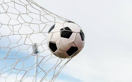 Voetbal voetbal in Doel netto met hemel veld Stockfoto