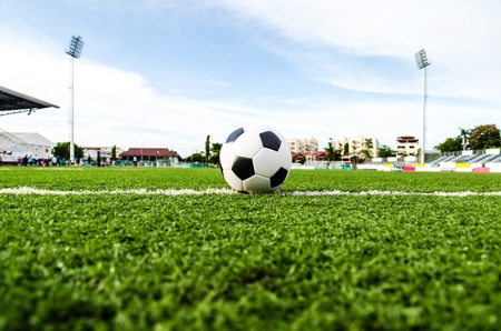 football match lawns: Soccer Football on line of Soccer field with player playing soccer