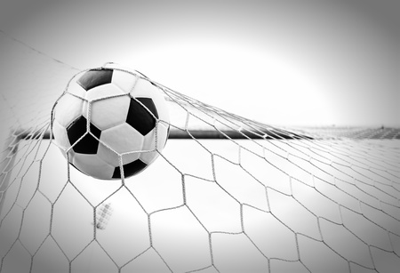 Soccer football in Goal net with sky field  photo