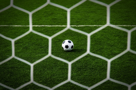 Soccer football in net with green grass field  photo