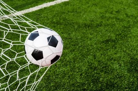cancha deportiva futbol: Balompié en red de la portería con el campo de hierba verde Foto de archivo