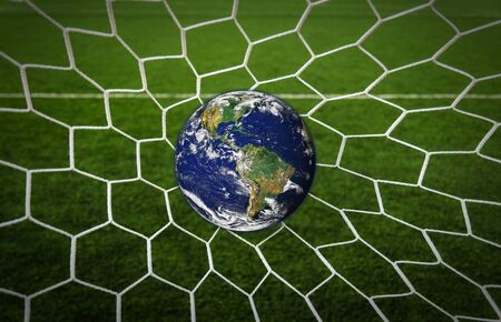 Earth Globe in Goal net with green grass field photo