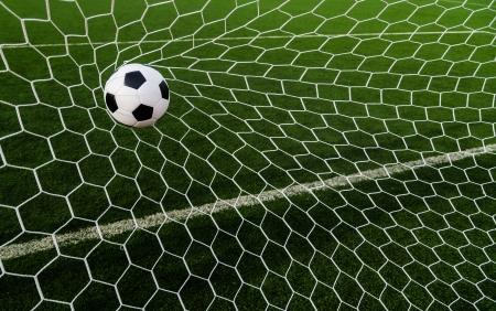 the net: Soccer football in Goal net with green grass field