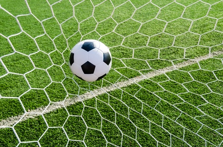 Soccer football in Goal net with green grass field  photo