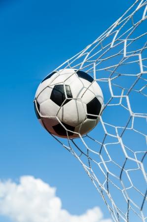 Soccer football in Goal net with sky field