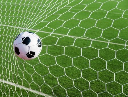 football goal: Soccer football in Goal net with green grass field