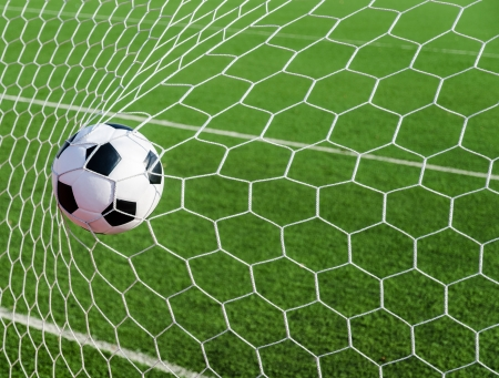 Voetbal voetbal in Doel netto met groen gras veld Stockfoto