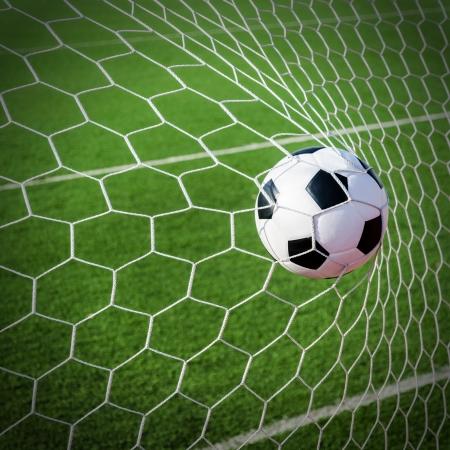 sport balls: Soccer football in Goal net with green grass field