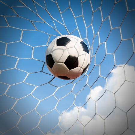 Soccer football in Goal net with Blue sky field  photo