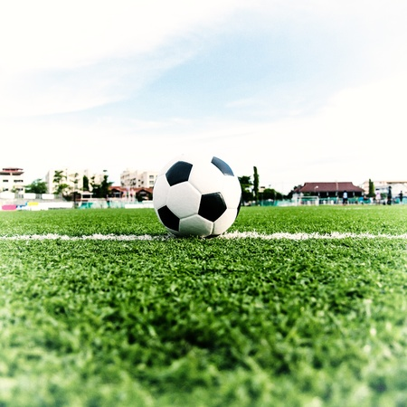 Voetbal voetbal op het groene gras van het voetbal veld met speler voetballen