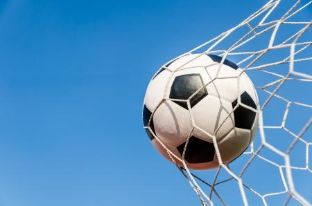 goal line: Soccer football in Goal net with Blue sky field  Stock Photo