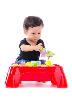 Schattige kleine jongen spelen speelgoed geïsoleerd op de witte achtergrond.