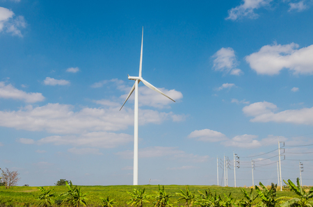 Wind turbine on the blue sky field. Stock Photo