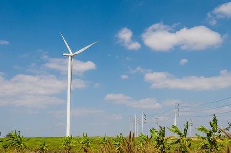 energy work: Wind turbine on the blue sky field. Stock Photo