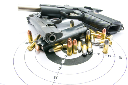 Gun and Bullets on shooting range Isolated on the white background. Stock Photo