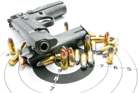Pistolet i kule na strzelnicy izolowany na białym tle.