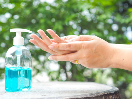 Woman's hands is pressing a bottle of Alcohol Gel to clean her hands. Alcohol gel is very important in daily life.