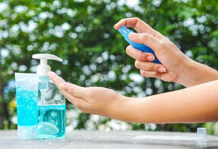 Woman's hand pressing Alcohol Spray in the nature for clean her hand. Alcohol Spray is very important in daily life.