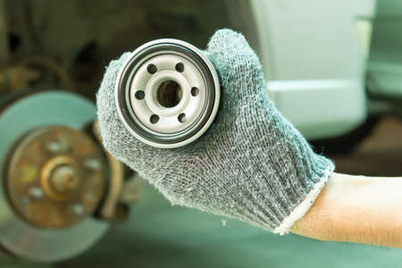 Hand with New oil Filter. 免版税图像