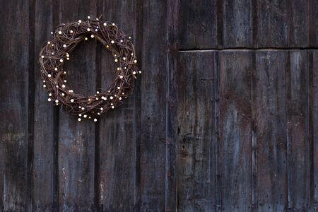 Advent wreath  with little light bulbs hanging on an old rough wooden door
