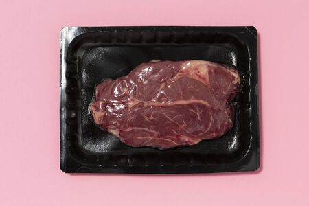 Black plastic pack with fresh beef steak isolated on pink background. Raw meat packed without label top view, vacuum packed