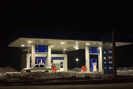 Kind on a gasoline station in the winter at night