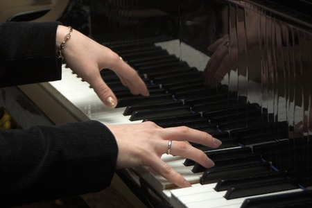 Hands of the pianist playing on a piano