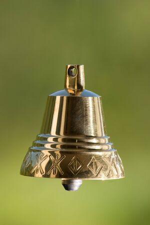 Four brass handbell on a green background photo