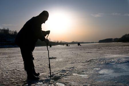 The fisherman on winter fishing drills ice Stock Photo - 2781007
