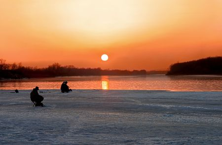 Two fishermen fish in the evening on a sunset Stock Photo - 2781006