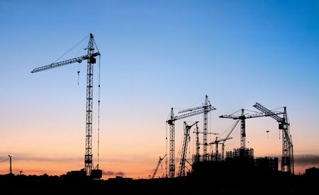 Silhouettes of tower cranes on a background of a decline