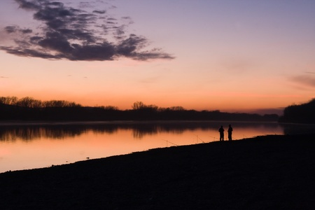 Silhouettes of fishermen on a background of an evening dawn Stock Photo - 8355376