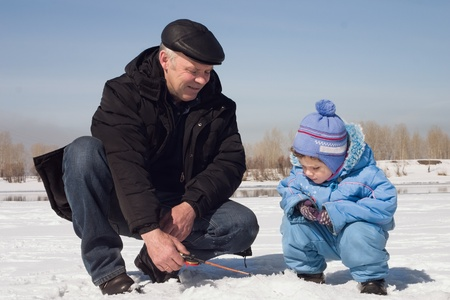 The boy, the child with the father on on winter fishing Stock Photo